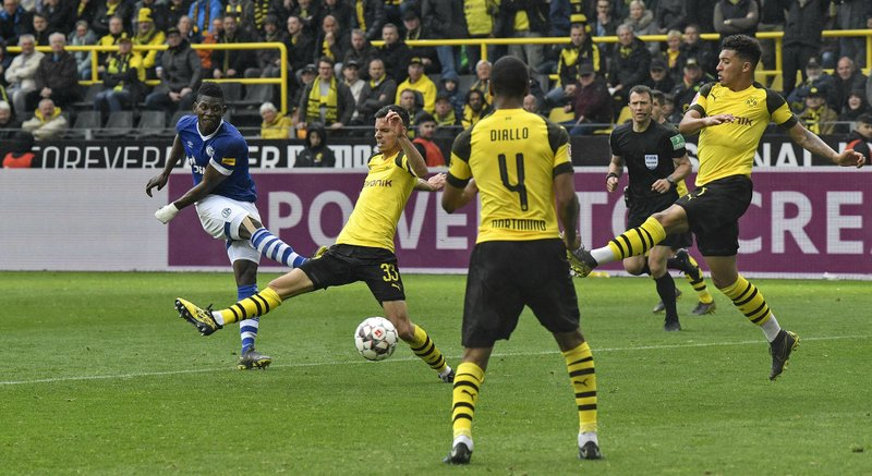 Schalke's Breel Embolo, left, scores his side's 4th goal during the German Bundesliga soccer match between Borussia Dortmund and FC Schalke 04 in Dortmund, Germany, Saturday, April 27, 2019. (AP Photo/Martin Meissner)