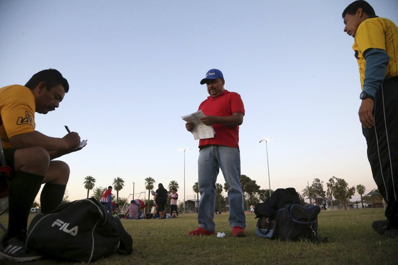 Antonio Velasquez, middle, a pastor and director of the Maya Chapin soccer league of over 108 teams, gives referees their game assignments Wednesday, April 17, 2019, in Phoenix. (AP Photo/Ross D. Franklin)