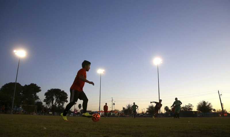 Adelfo Guillermo Martin Perez, 24, an arrival in the United States for three months and originally from Guatemala, dribbles the ball at a Maya Chapin soccer league game Wednesday, April 17, 2019, in Phoenix. (AP Photo/Ross D. Franklin)