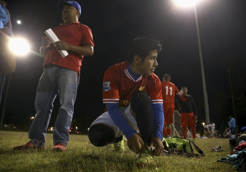 Pedro Chilel, 21, abandoned by his parents in Guatemala before he traveled alone to the United States at age 17, ties his shoes before his Maya Chapin soccer league game Wednesday, April 17, 2019, in Phoenix. (AP Photo/Ross D. Franklin)