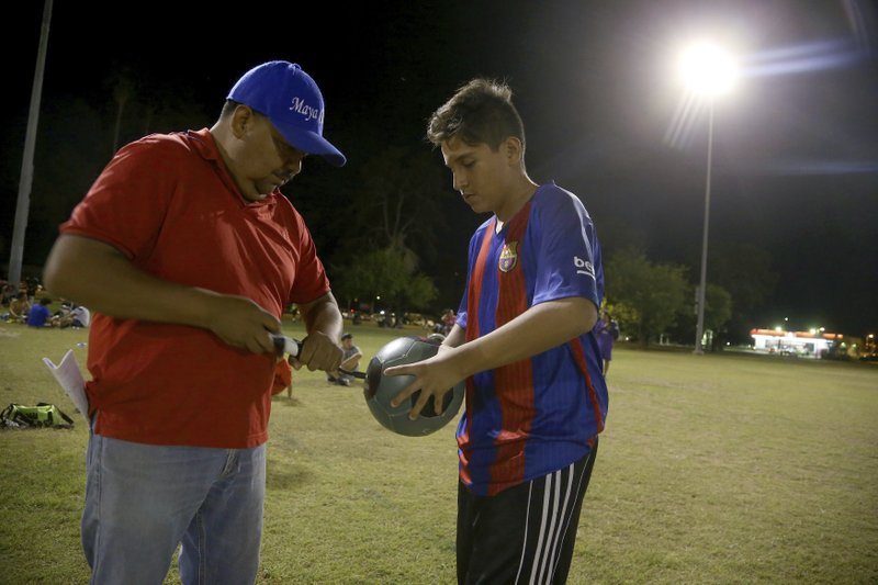 Antonio Velasquez, left, a pastor and director of the Maya Chapin soccer league of over 108 teams, helps inflate a soccer ball at a soccer league game Wednesday, April 17, 2019, in Phoenix. (AP Photo/Ross D. Franklin)