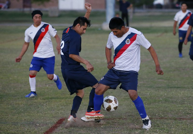 Two players battle for the ball during a Maya Chapin soccer league game Wednesday, April 17, 2019, in Phoenix. (AP Photo/Ross D. Franklin)