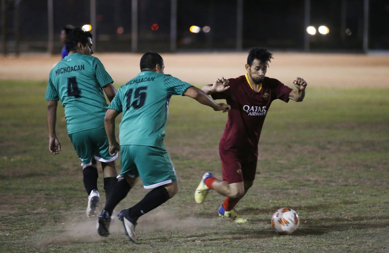 Players battle for control of the ball at a Maya Chapin soccer league game Wednesday, April 17, 2019, in Phoenix. (AP Photo/Ross D. Franklin)