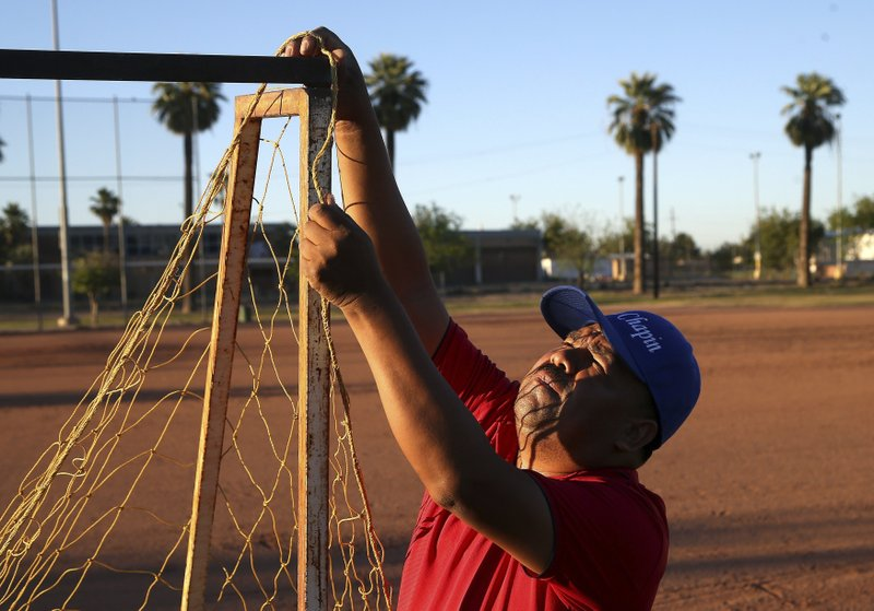 Antonio Velasquez, a pastor and director of the Maya Chapin soccer league of over 108 teams, prepares a goal net prior to the night games Wednesday, April 17, 2019, in Phoenix. (AP Photo/Ross D. Franklin)
