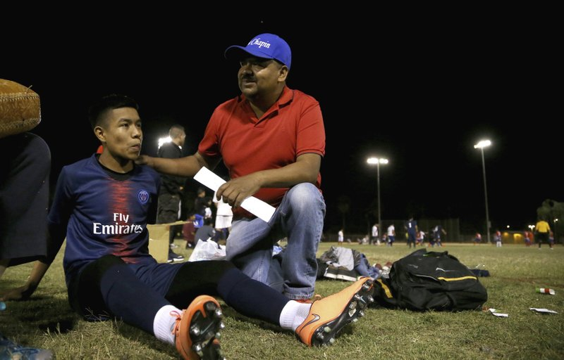 Antonio Velasquez, right, a pastor and director of the Maya Chapin soccer league, talks with player William Sebastian, 16, left, during a break in a soccer league game Wednesday, April 17, 2019, in Phoenix. (AP Photo/Ross D. Franklin)