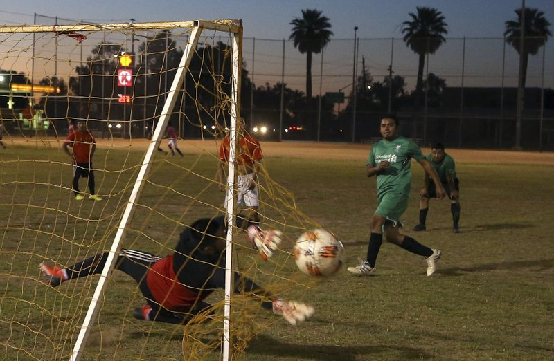 A member of the Michoacan team, right, scores a goal at a Maya Chapin soccer league game Wednesday, April 17, 2019, in Phoenix. (AP Photo/Ross D. Franklin)