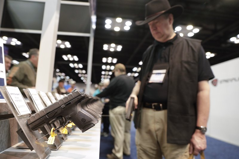 A gun enthusiast looks over the display of Beretta pistols on display in the exhibition hall at the National Rifle Association Annual Meeting in Indianapolis, Saturday, April 27, 2019. (AP Photo/Michael Conroy)