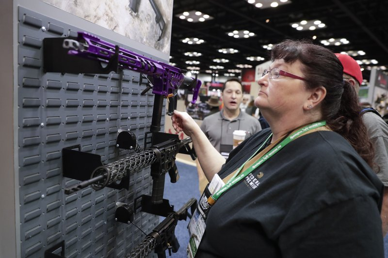 A gun enthusiast looks at rifles from Lead Star Arms in the exhibition hall at the National Rifle Association Annual Meeting in Indianapolis, Saturday, April 27, 2019. (AP Photo/Michael Conroy)