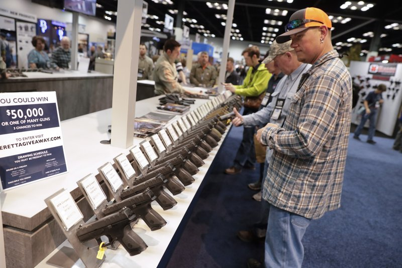 A gun enthusiast look over the display of Beretta pistols in the exhibition hall at the National Rifle Association Annual Meeting in Indianapolis, Saturday, April 27, 2019. (AP Photo/Michael Conroy)