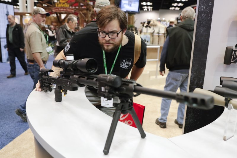 Evan Downey of Gallipolis, Ohio looks over a rifle display in the exhibition hall at the National Rifle Association Annual Meeting in Indianapolis, Saturday, April 27, 2019. (AP Photo/Michael Conroy)
