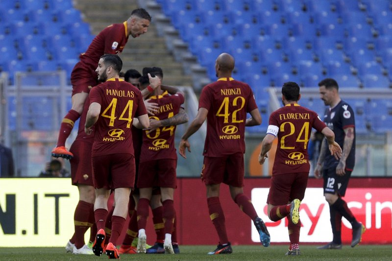 Roma players celebrate after their teammate Javier Pastore scored his side's second goal during a Serie A soccer match between Roma and Cagliari, at Rome's Olympic Stadium, Saturday, April 27, 2019. (AP Photo/Gregorio Borgia)