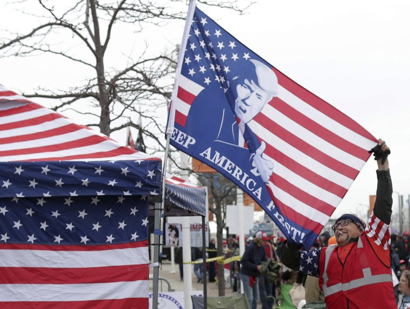 Randal Thom, Lakefield Minn., adjusts a flag while waiting in line before President Donald J. Trump's Make America Great Again Rally on Saturday, April 27, 2019, at the Resch Center in Green Bay, Wis. (Wm. Glasheen/The Post-Crescent via AP)