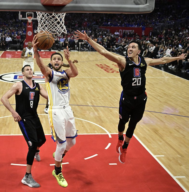 Golden State Warriors guard Stephen Curry, center, shoots as Los Angeles Clippers forward Danilo Gallinari, left, and guard Landry Shamet defend during the second half in Game 6 of a first-round NBA basketball playoff series Friday, April 26, 2019, in Los Angeles. (AP Photo/Mark J. Terrill)