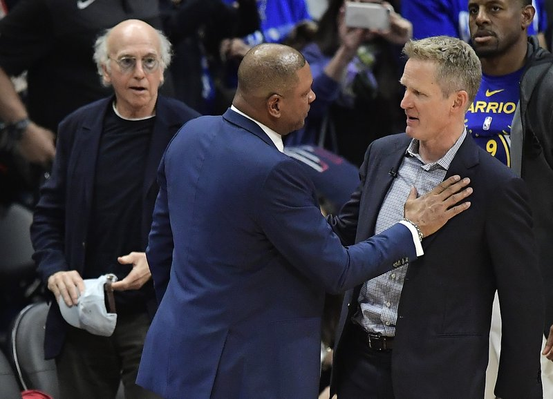 Los Angeles Clippers head coach Doc Rivers, center, and Golden State Warriors head coach Steve Kerr, right, congratulate each other as actor Larry David looks on after Game 6 of a first-round NBA basketball playoff series Friday, April 26, 2019, in Los Angeles. (AP Photo/Mark J. Terrill)
