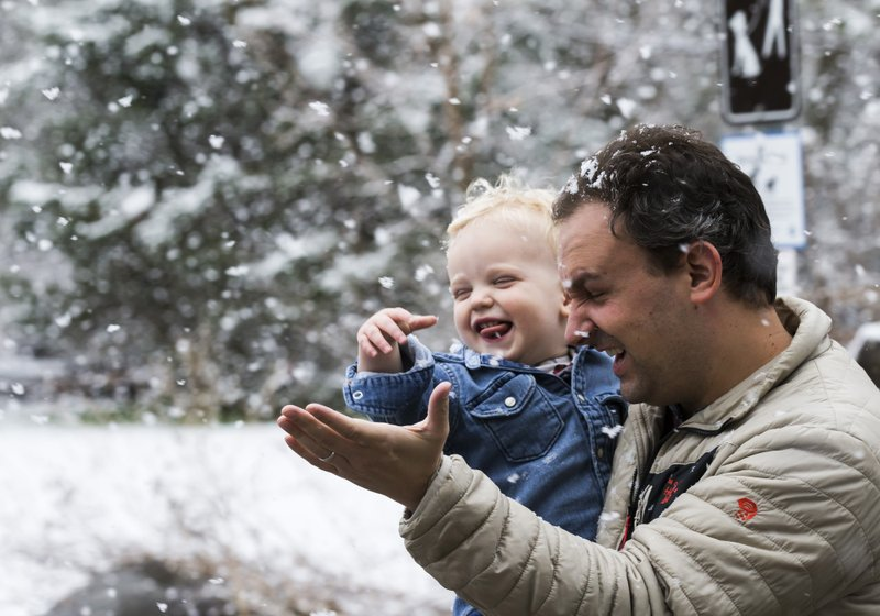 John Giudicessi and his one-year-old son, Hugo, try to catch snowflakes while walking to their car after visiting the Quarry Hill Nature Center on Saturday, April 27, 2019, in Rochester, Minn. (Andrew Link/The Rochester Post-Bulletin via AP)