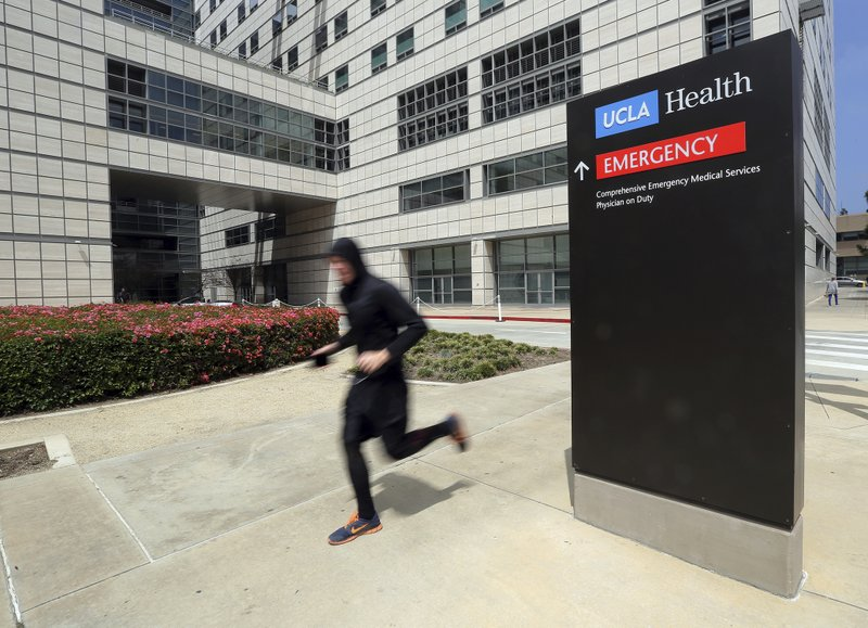 A runner passes the Ronald Reagan UCLA Medical Center on the campus of the University of California, Los Angeles Friday, April 26, 2019. (AP Photo/Reed Saxon)