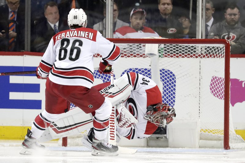 Carolina Hurricanes goaltender Petr Mrazek, right, of the Czech Republic, falls to the ice while blocking a shot from the New York Islanders during the third period of Game 1 of an NHL hockey second-round playoff series, Friday, April 26, 2019, in New York. (86), of Finland, looks on during the play. (AP Photo/Julio Cortez)