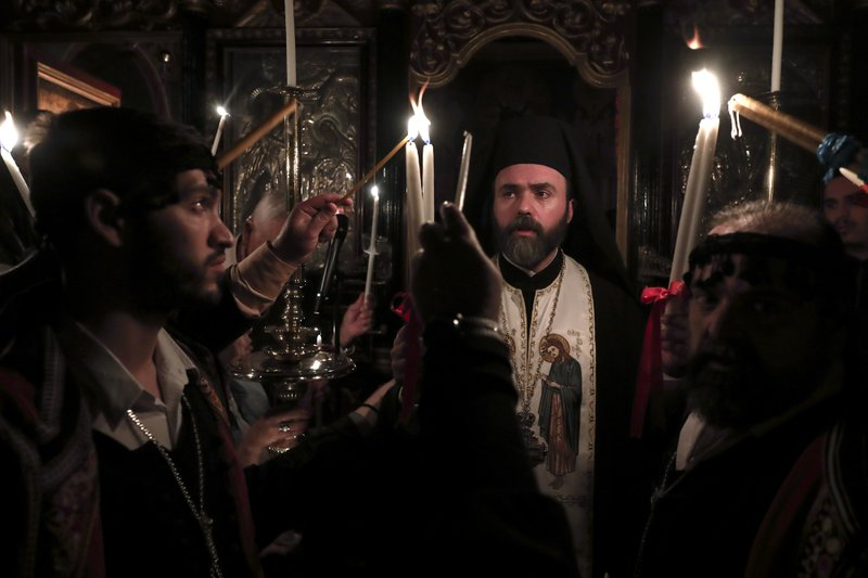 A Greek Orthodox priest lights candles of the faithful with Holy Fire brought from Jerusalem, at a church in Athens, on Saturday, April 27, 2019. (AP Photo/Yorgos Karahalis)