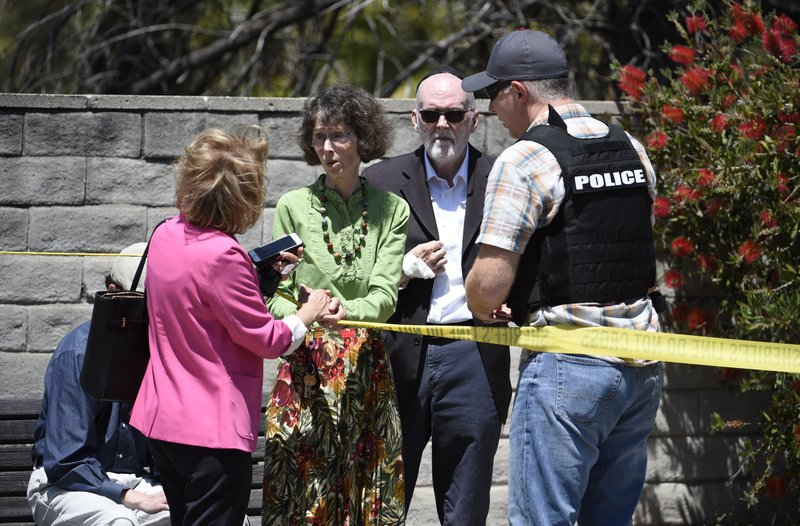 Synagogue members talk to a San Diego County Sheriff's deputy outside of the Chabad of Poway Synagogue Saturday, April 27, 2019, in Poway, Calif. (AP Photo/Denis Poroy)