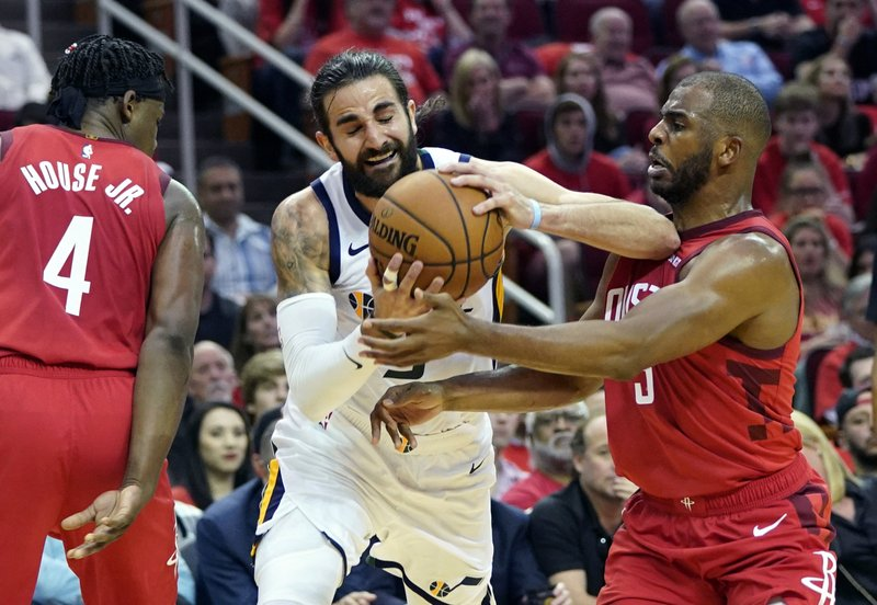 Utah Jazz guard Ricky Rubio, center, is defended by Houston Rockets guard Chris Paul, right, during the second half in Game 5 of an NBA basketball playoff series, in Houston, Wednesday, April 24, 2019. (AP Photo/David J. Phillip)