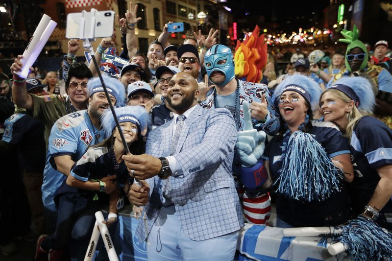 Tennessee Titans player Jurrell Casey takes a photo with fans on the main stage after announcing the Titans selection of North Carolina-Charlotte guard Nate Davis during the third round of the NFL football draft, Friday, April 26, 2019, in Nashville, Tenn. (AP Photo/Mark Humphrey)