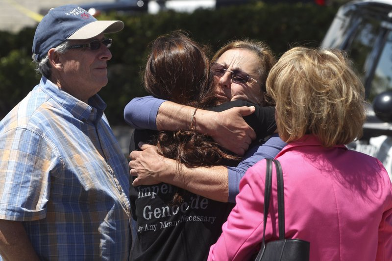 Members of the Chabad synagogue hug as they gather near the Altman Family Chabad Community Center, Saturday, April 27, 2019 in Poway, Calif. (Hayne Palmour IV/The San Diego Union-Tribune via AP)