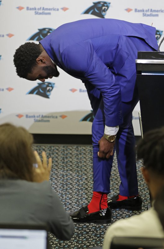 Carolina Panthers draft choice Brian Burns pulls up his pants leg to show off his Spiderman socks during a news conference for the NFL football team in Charlotte, N. (AP Photo/Chuck Burton)