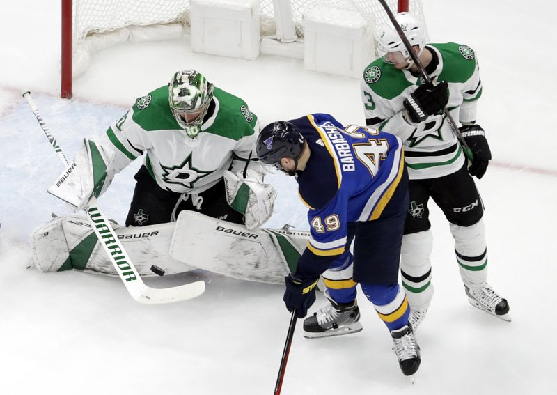 Dallas Stars goaltender Ben Bishop, left, deflects a puck as teammate John Klingberg, right, and St. Louis Blues' Ivan Barbashev (49), of Russia, watch during the first period in Game 2 of an NHL second-round hockey playoff series Saturday, April 27, 2019, in St. (AP Photo/Jeff Roberson)