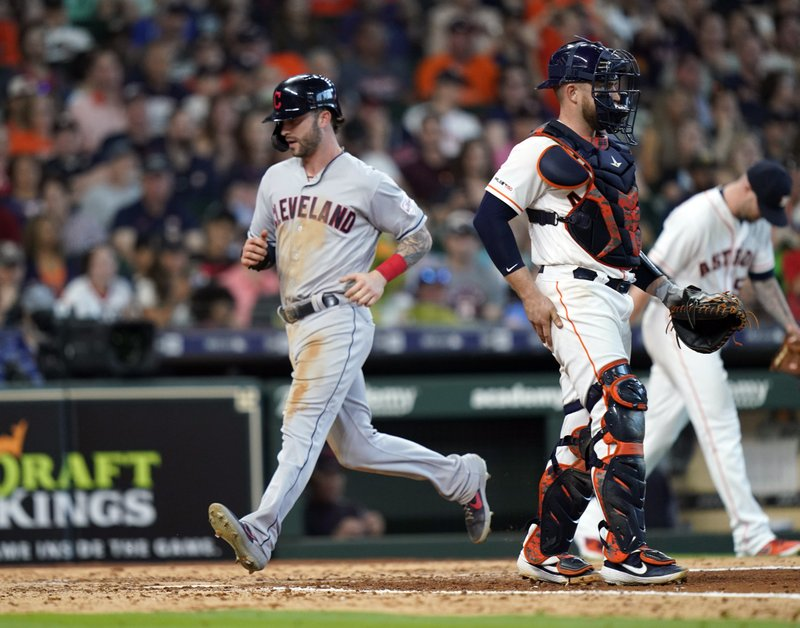Cleveland Indians' Tyler Naquin, left, scores as Houston Astros catcher Max Stassi stands in front of home plate during the seventh inning of a baseball game Saturday, April 27, 2019, in Houston. (AP Photo/David J. Phillip)