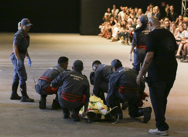 Model Tales Soares is taken from the catwalk by paramedics after he collapsed during Sao Paulo Fashion Week in Sao Paulo, Brazil, Saturday, April 27, 2019. (Leco Viana/Thenews2 via AP)