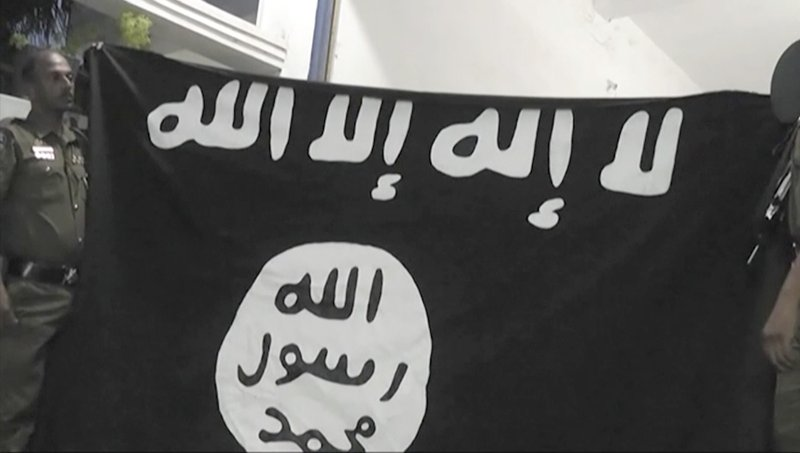 In this Friday, April 26, 2019, image made from video, officers hold up an Islamic State group flag in Arabic that reads: