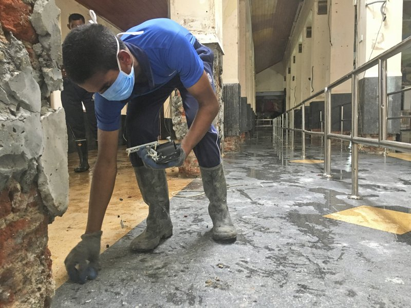 A Sri Lankan Naval soldier picks up the small pieces of glass from inside of the damaged St. Anthony's Church in Colombo, Saturday, April 27, 2019. (AP Photo/Shonal Ganguly)