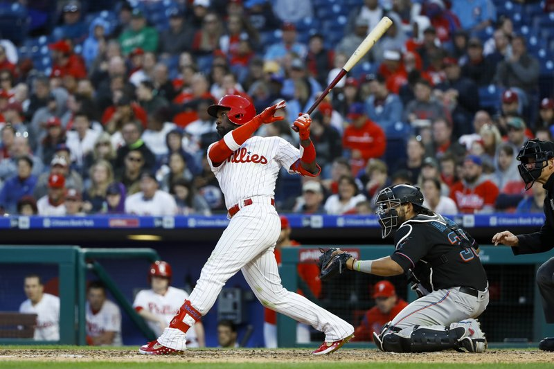 Philadelphia Phillies' Andrew McCutchen, left, follows through after hitting a home run off Miami Marlins starting pitcher Trevor Richards during the fourth inning of a baseball game, Saturday, April 27, 2019, in Philadelphia. (AP Photo/Matt Slocum)