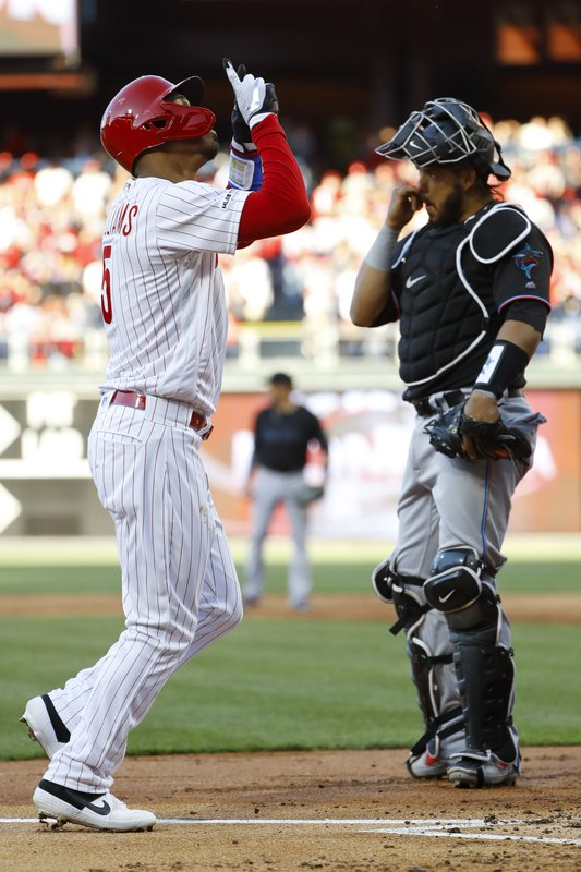 Philadelphia Phillies' Nick Williams, left, reacts while passing Miami Marlins catcher Jorge Alfaro, right, after hitting a home run off starting pitcher Trevor Richards during the second inning of a baseball game, Saturday, April 27, 2019, in Philadelphia. (AP Photo/Matt Slocum)