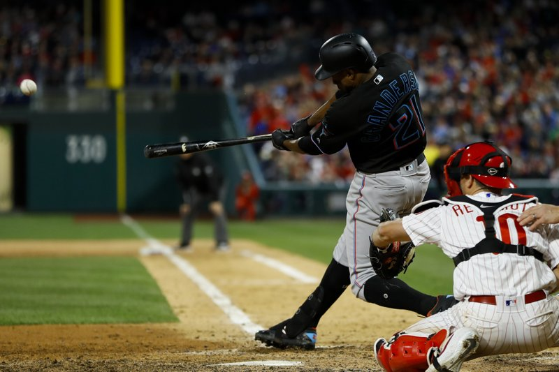 Miami Marlins' Curtis Granderson, left, follows through after hitting a two-run double off Philadelphia Phillies relief pitcher Jose Alvarez during the sixth inning of a baseball game, Saturday, April 27, 2019, in Philadelphia. (AP Photo/Matt Slocum)