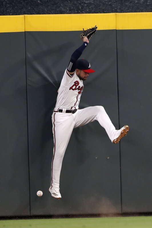 Atlanta Braves center fielder Ender Inciarte canno reach a ball hit for a triple by Colorado Rockies' David Dahl in the seventh inning of a baseball game Saturday, April 27, 2019, in Atlanta. (AP Photo/John Bazemore)