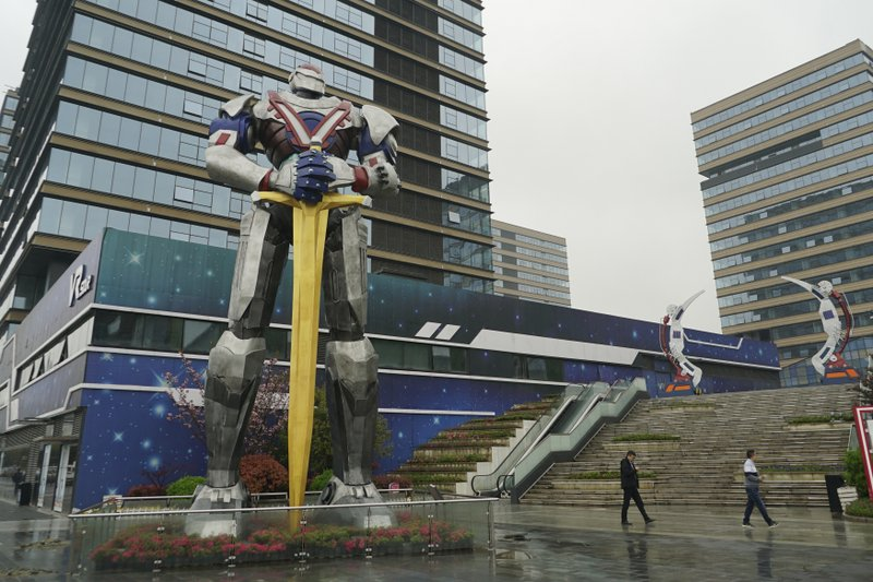 In this April 2, 2019, photo, people walk by a giant robot statue at a virtual reality