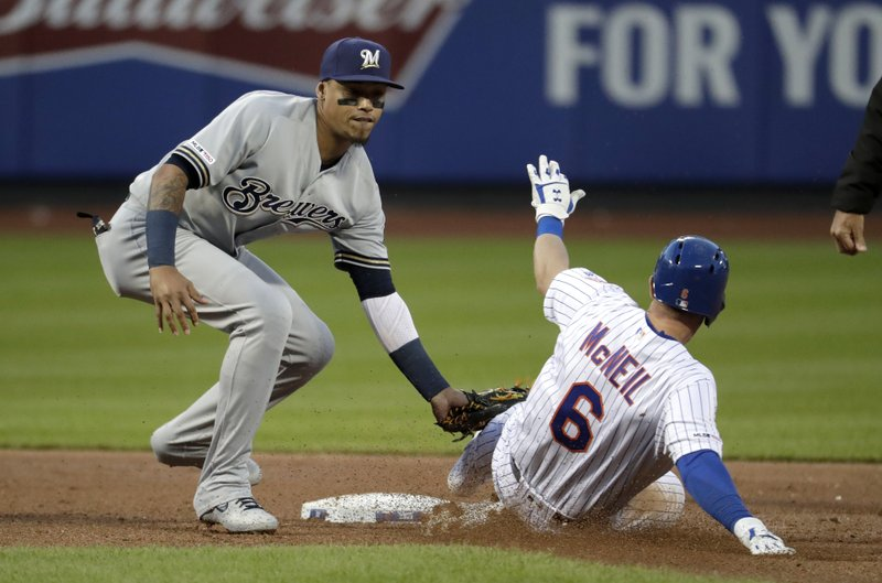 Milwaukee Brewers shortstop Orlando Arcia, left, tags out New York Mets' Jeff McNeil who was trying to steal second base to end the first inning of a baseball game, Saturday, April 27, 2019, in New York. (AP Photo/Julio Cortez)