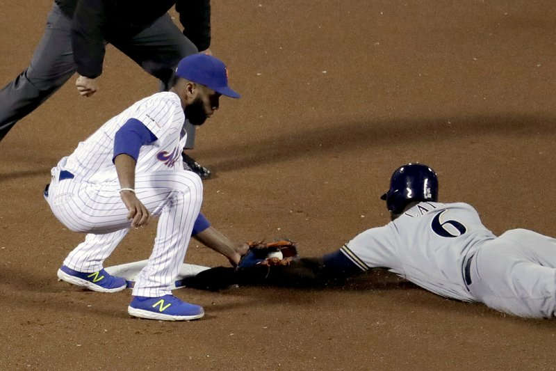 New York Mets shortstop Amed Rosario, left, tags out Milwaukee Brewers' Lorenzo Cain who was trying to steal second base during the fourth inning inning of a baseball game, Saturday, April 27, 2019, in New York. (AP Photo/Julio Cortez)