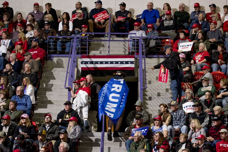 An audience member wears a Trump flag as a cape as he walks in the bleachers during a speech by President Donald Trump at Resch Center Complex in Green Bay, Wis. (AP Photo/Andrew Harnik)