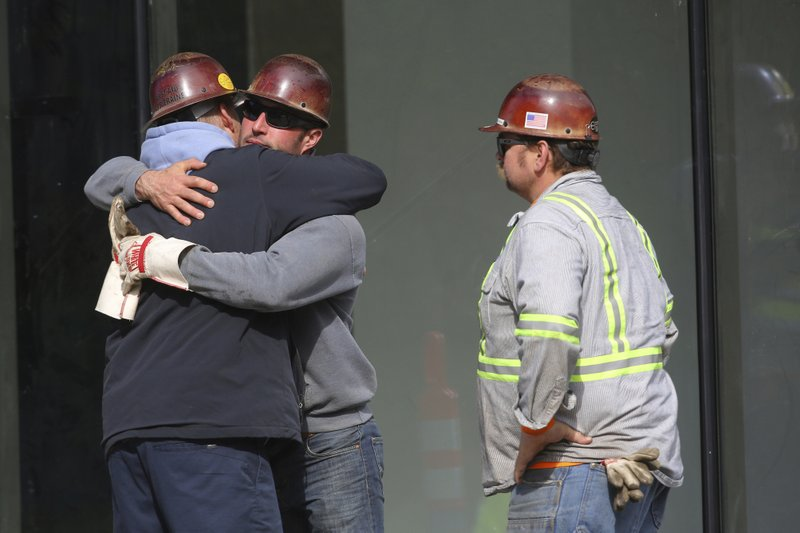 Workers hug at the scene after a construction crane working on a building on Mercer Street collapsed, Saturday, April 27, 2019, in downtown Seattle. (Genna Martin/seattlepi.com via AP)