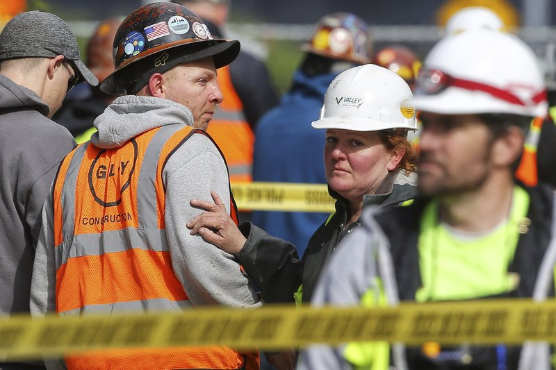 Construction workers wait at the scene after a crane working on a building collapsed on Mercer Street near Interstate 5 Saturday, April 27, 2019, in Seattle. (Genna Martin/seattlepi.com via AP)