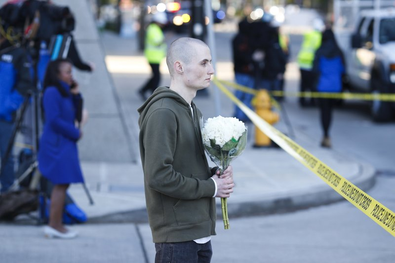 Blake Haner, a Seattle resident, holds flowers for those who died at the scene of a construction crane collapse where several people were killed and several others injured Saturday, April 27, 2019, in the South Lake Union neighborhood of Seattle. (AP Photo/Joe Nicholson)