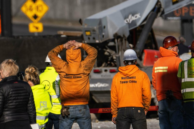 Police investigate the scene of a construction crane collapse near the intersection of Mercer Street and Fairview Avenue Saturday, April 27, 2019, in Seattle. (Dean Rutz/The Seattle Times via AP)
