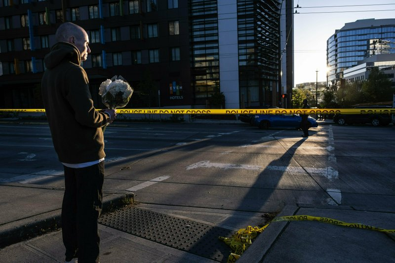 Blake Haner stands near the scene of the accident with flowers and an expression of condolence for those killed in a construction crane collapse near the intersection of Mercer Street and Fairview Avenue Saturday, April 27, 2019, in Seattle. (Dean Rutz/The Seattle Times via AP)