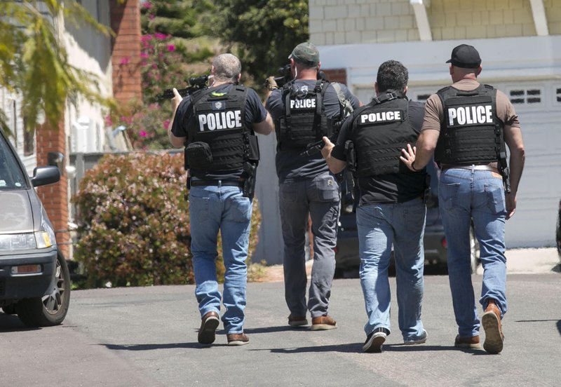 Heavily armed San Diego police officers approach a house thought to be the home of 19 year-old John T. (John Gibbins/The San Diego Union-Tribune via AP)
