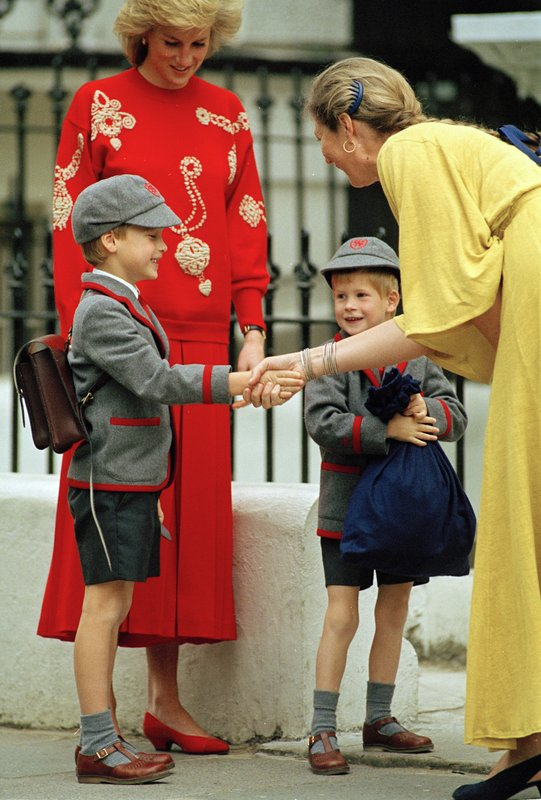 FILE - In this Sept. 11, 1989 file photo, Britain's Prince William gets a handshake from Frederika Blair-Turner, the headmistress of Wetherby School in Notting Hill as his little brother Prince Harry, 4, smiles, clutching his schoolbag with their mother, Diana, the Princess Diana of Wales in the background. (AP Photo/Gill Allen, File)