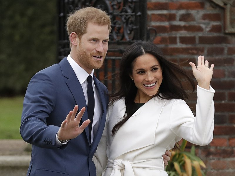 FILE - In this Monday, Nov. 27, 2017 file photo, Britain's Prince Harry and his fiancee Meghan Markle pose for photographers during a photocall in the grounds of Kensington Palace in London. (AP Photo/Matt Dunham, File)