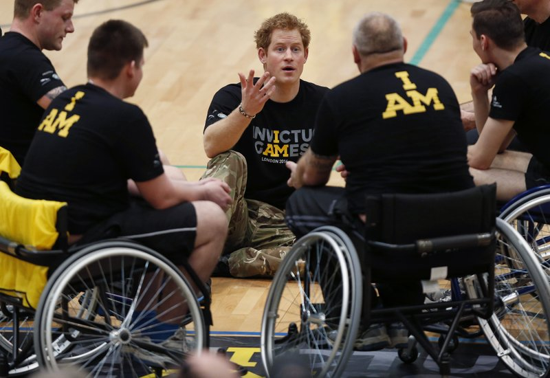 FILE - In this Thursday, March 6, 2014 file photo, Britain Prince Harry, center, speaks to the wheelchair basketball competitors during the launch of the Invictus Games for wounded warriors at the Copper Box arena in the Queen Elizabeth Olympic Park in London. (AP Photo/Sang Tan, File)