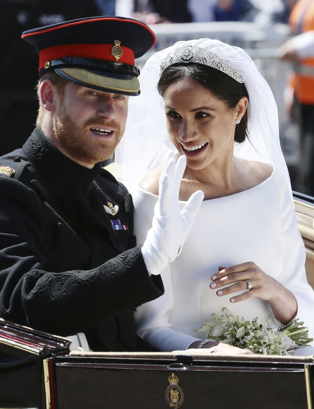 FILE - In this Saturday, May 19, 2018 file photo, Britain's Prince Harry and Meghan Markle ride in an open-topped carriage after their wedding ceremony at St. (Aaron Chown/pool photo via AP, File)